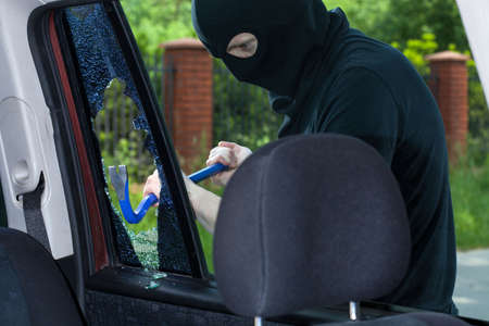 A burglar breaks a window with a crowbar in the car photo