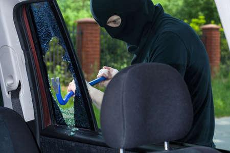 A burglar breaks a window with a crowbar in the car