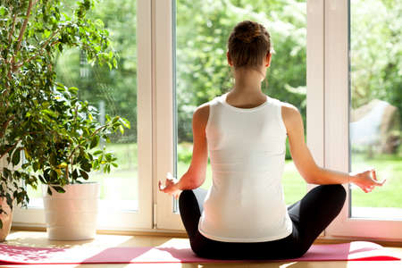 Horizontal view of a woman doing yoga at home photo