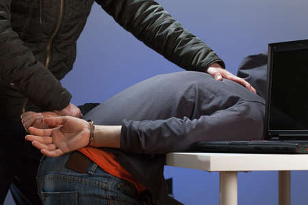 overpowered: An overpowered hacker being arrested by the police Stock Photo