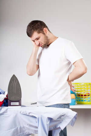 A clumsy man not knowing how to iron clothes photo