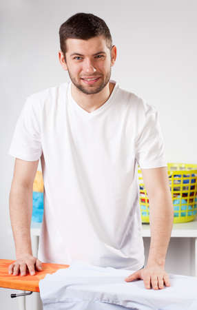 A man fulfiling household duties like ironing or laundry photo