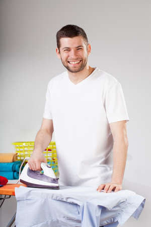 A happy man smiling while ironing clothes photo