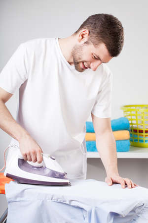 household chores: A handsome man doing the ironing as his chore