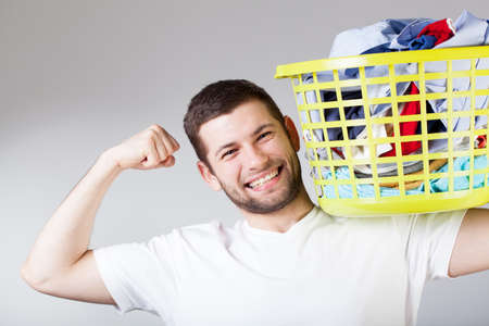 doing laundry: A smiling strong handsome man doing the laundry Stock Photo