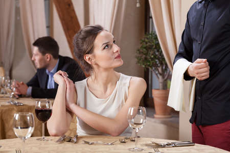 dinner date: Woman ordering meal in a restaurant, horizontal