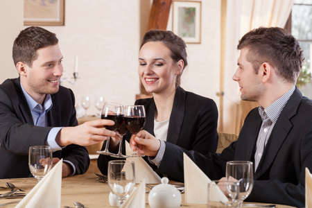 business dinner: Friends drinking wine in a restaurant, horizontal Stock Photo