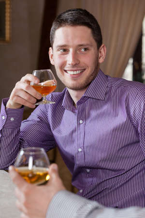 Man drinking cognac with his friend, vertical photo