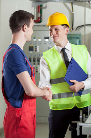 construction manager: Vertical view of a handshake in a factory