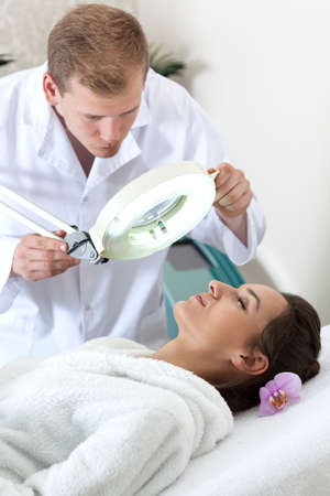 cosmetologist: Male cosmetologist examining patients skin condition, vertical
