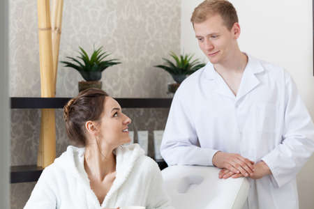 cosmetologist: Male cosmetologist and woman talking at spa salon Stock Photo