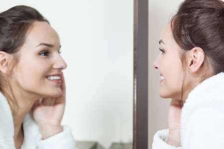 Young woman watching in mirror her skin condition after treatments photo