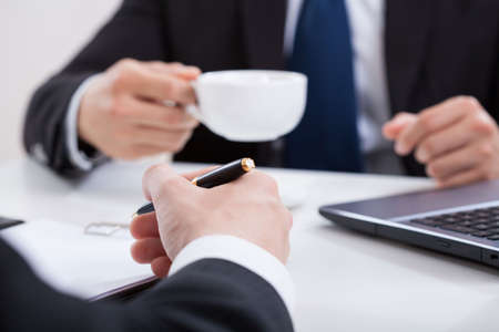 Man drinking coffee on a business meeting photo