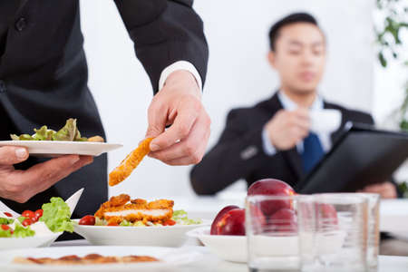 business dinner: Asian men during business lunch in the office Stock Photo