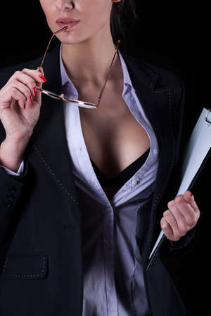 Sexy businesswoman with unbuttoned shirt holding glasses photo