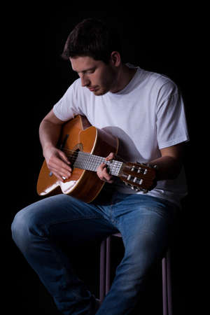 guitar player: Portrait of a young man in casual clothes playing guitar Stock Photo
