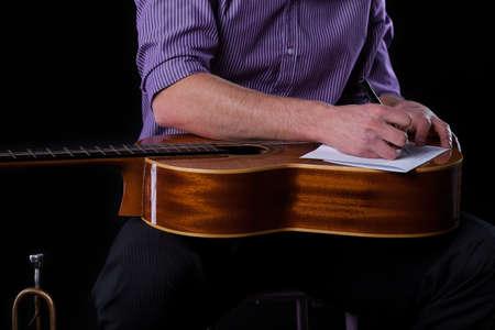 letras musicales: Primer plano de un guitarrista de escribir una canción, horizontal
