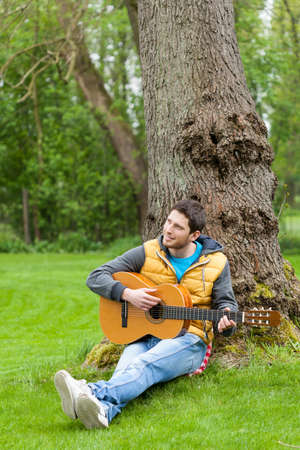 air guitar: Young man sitting on grass and playing guitar