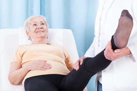 pierna rota: Mujer de edad avanzada durante la rehabilitación de la pierna en el hospital
