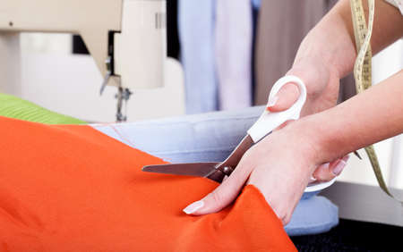 precisely: Tailor cutting orange fabric with scissors very precisely Stock Photo