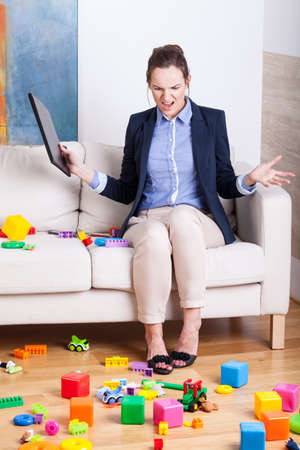 Furious woman sitting on a sofa in a room full of kids toys photo