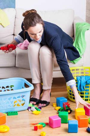 madre trabajando: Señora que trabaja limpiando juguetes de los niños de colores Foto de archivo
