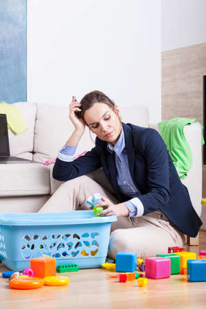 Tired woman cleaning up room from kids toys photo