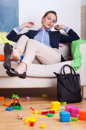 habitacion desordenada: Empresaria después del trabajo, sentado en el sofá en la habitación desordenada en casa Foto de archivo