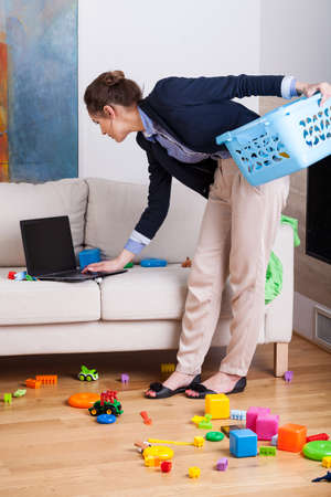 multitask: Young elegant woman working on her laptop during cleaning up living room