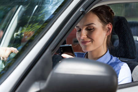 Close-up of a smiling woman texting on mobile phone during driving a car photo