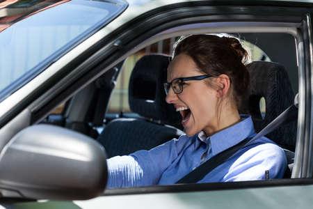 Jonge elegante vrouw het stoppen van de auto en schreeuwen