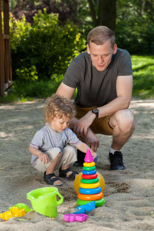 sandpit: Dad and son having fun on playground