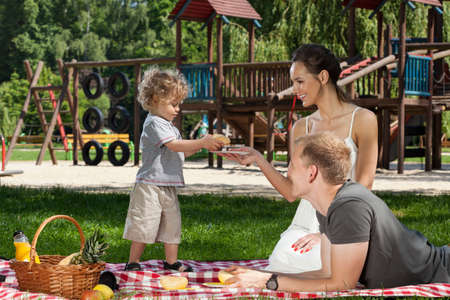 picnic blanket: Boy giving mom a roll on family picnic