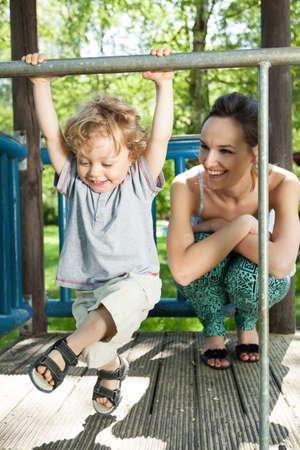 Little boy swinging on monkey bars on playground