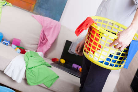 Businessman cleaning up home and doing laundry photo