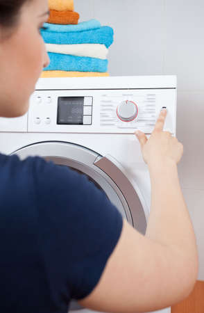 Housekeeper turning on the washing machine, vertical photo