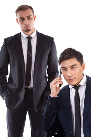 Asian businessman talking on the phone and caucasian besides him photo