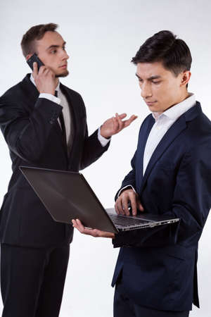 Two businessman during work with phone and computer photo