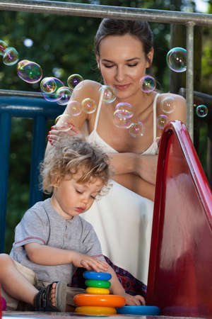 Mother and son playing with toys on playground photo