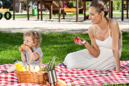 having lunch: Mother and little baby having family picnic Stock Photo