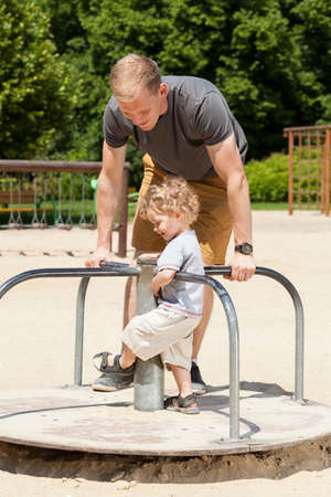 merry go round: Dad and son playing on merry-go-round on playground