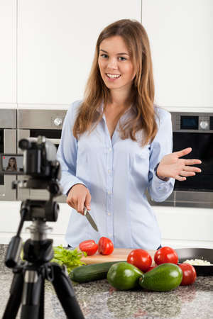 meal preparation: Attractive woman filming her meal preparation, vertical