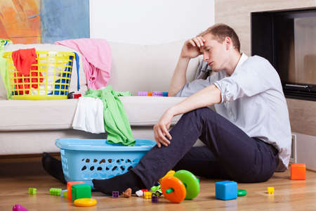 tired businessman: Lonly tired father sitting with childs toys Stock Photo