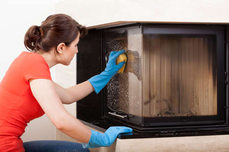 Horizontal view of housekeeper cleaning the fireplace