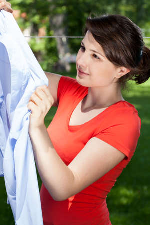 hang up: Woman hanging the laundry in a garden
