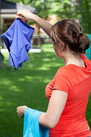 Young mum hanging the laundry in a garden photo