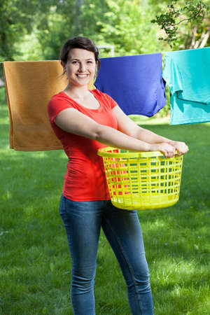 Smiling woman with laundry in a garden photo