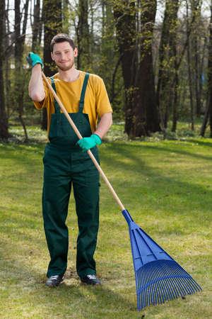 ハンサムな若い男の庭で葉を掻き集める