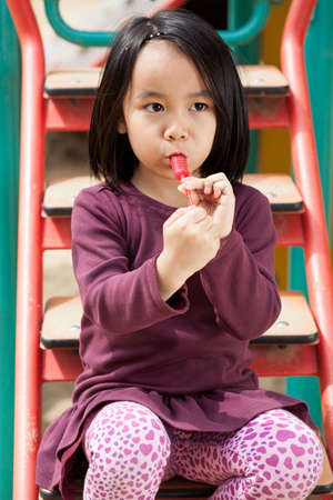 Little girl sitting on the slide and eating a lollipop photo