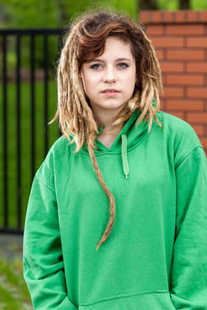 Young rude rasta girl with dreads in green blouse
